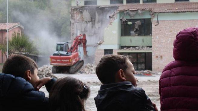 LACRIME La foto dei bambini che osservano la demolizione  della loro vecchia scuola è uno dei simboli del terremoto del 2016