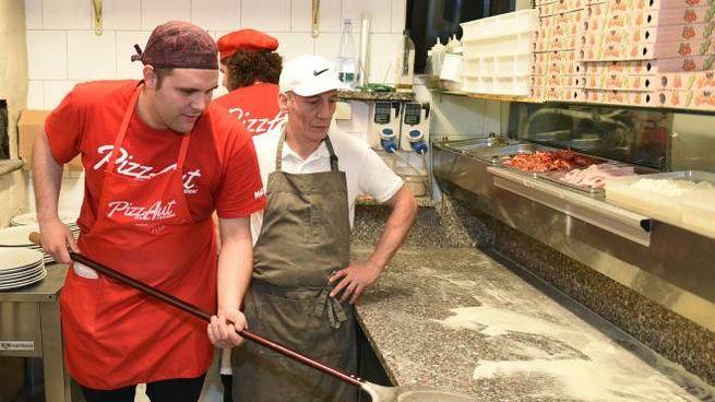 un ragazzo all'opera con una pizza