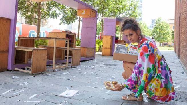 Una volontaria raccoglie i libri gettati in giro