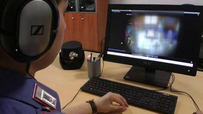 Un carabiniere esamina le immagini di una telecamera installata in un asilo