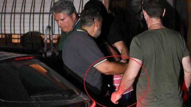 Logli, con la maglia rossa a righe, entra in auto per andare in carcere (Valtriani)