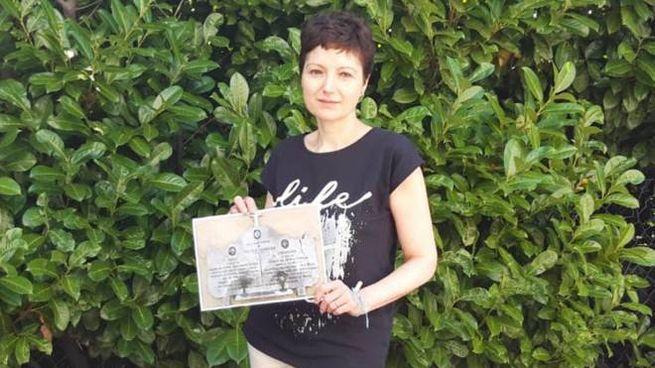 Simona con la fotografia della lapide dedicata ai fratelli Ferdinando e Paolo Monguzzi