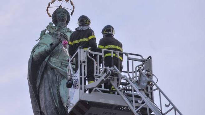 I vigili del fuoco donano i fiori alla statua della Madonna in piazza Malpighi (archivio)