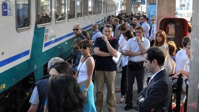 Studenti e lavoratori sulla banchina aspettano la partenza del treno