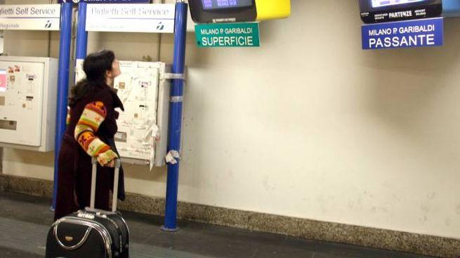 Una pendolare controlla i monitor del passante a Porta Garibaldi