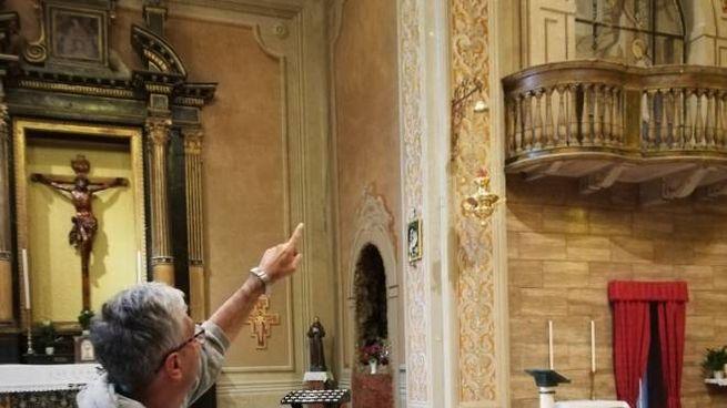 Don Luciano Domeneghetti indica il soffitto dove ieri si è staccato l'intonaco