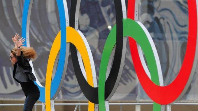 Una ragazza salta di fronte ai cinque cerchi olimpici