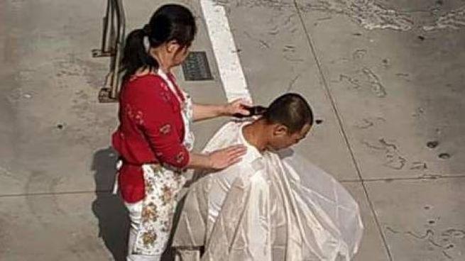 Sedia in strada: il barbiere taglia alla luce del sole