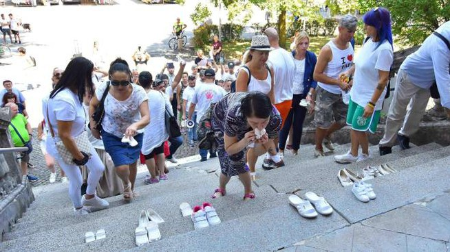 Scarpette bianche deposte davanti al municipio di Bibbiano (Foto Ansa)