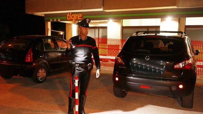 Un carabiniere all'esterno del supermercato della rapina