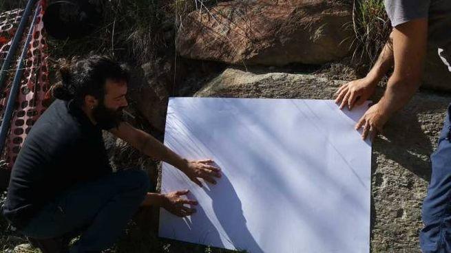 Gli esperti mentre analizzano da vicino la stele
