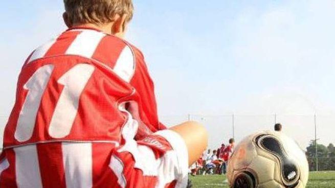 Un baby calciatore seduto accanto a un pallone