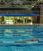 I teloni blu arrotolati che sovrastano l'area di bordo vasca nel Centro nuoto di Vignola