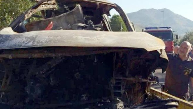 L'auto incendiata dopo l'incidente (Ansa)
