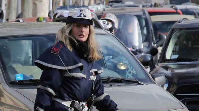 Una vigilessa impegnata a districare un ingorgo nella zona della stazione