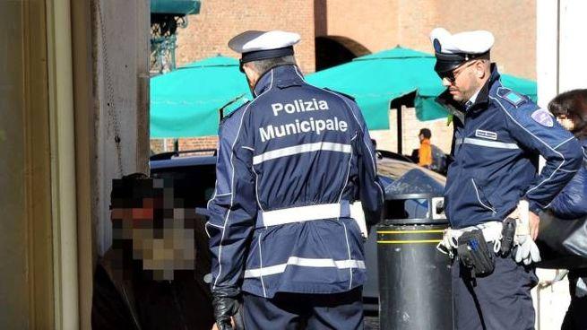 Gli agenti della municipale allontanano un mendicante (Foto di repertorio Businesspress)