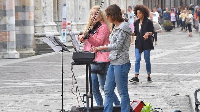 Artisti di strada durante un'esibizione in piazza Duomo