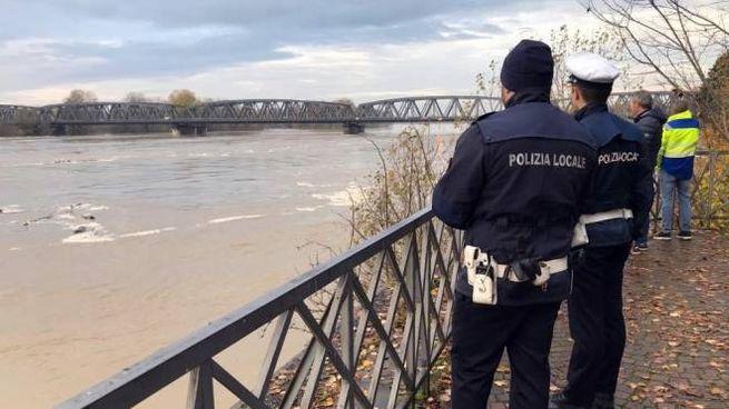 Agenti dell polizia locale osservano un tratto del fiume Po nei pressi di Cremona