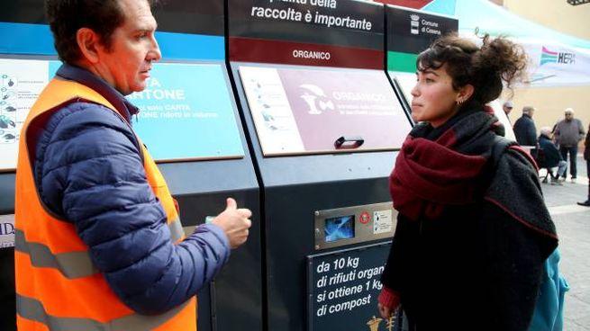 Un addetto spiega a una cittadina il corretto conferimento dei rifiuti con il sistema Ecos