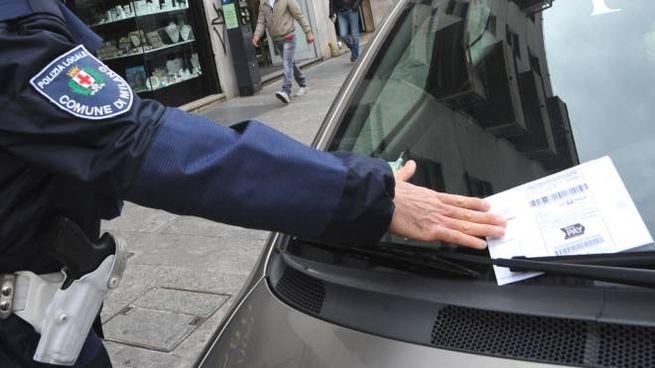 Un agente della polizia locale multa un'auto in sosta vietata in centro