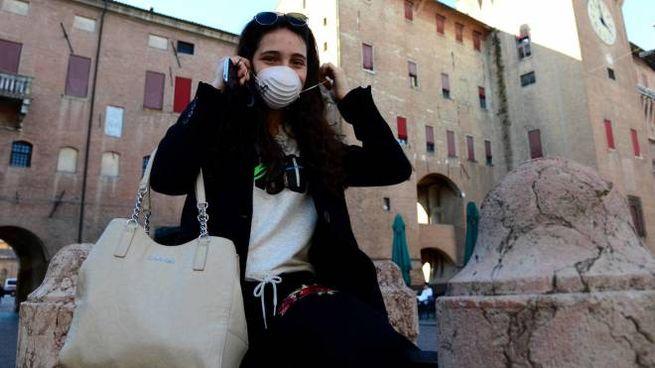 Una ragazza indossa la mascherina in piazza Savonarola