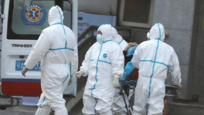 Personale medico trasferisce i pazienti infetti dal virus misterioso (Ansa)