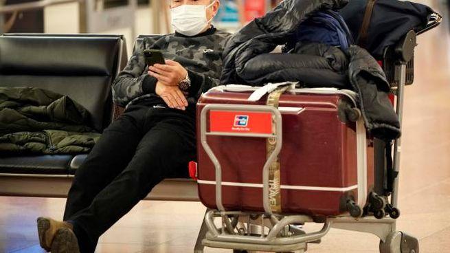 Viaggiatore con la mascherina in un aeroporto orientale