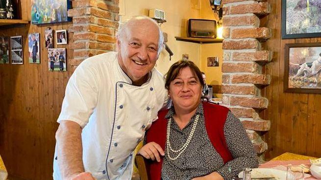 Mario Cattaneo, 69 anni, con una cliente tra i tavoli del suo locale