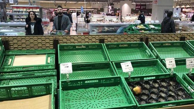 Scaffali ormai vuoti in un supermercato Coop (Ansa)