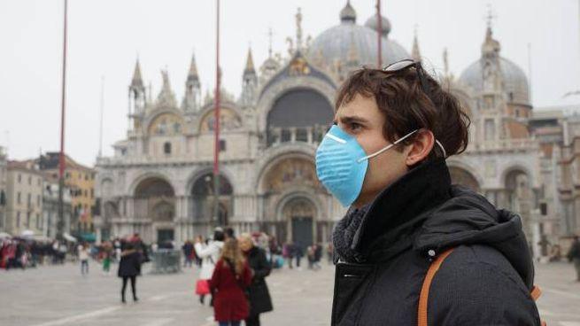 Un turisti con la mascherina a Venezia (Ansa)