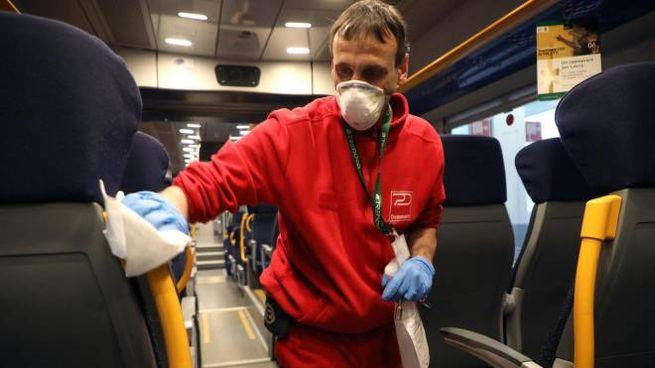 Operatore disinfetta i sedili alla stazione Garibaldi di Milano (Ansa)