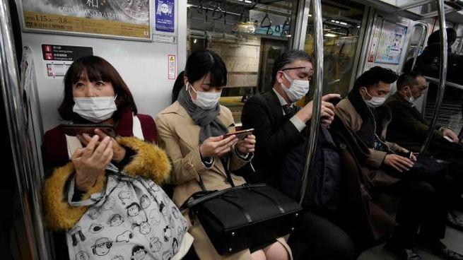 Persone con la mascherina nella metropolitana di Tokyo (Ansa)
