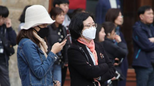 Turisti con mascherine a Firenze (foto NewPressPhoto)