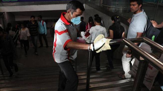Un addetto alle pulizie nella metro di Delhi (India). Foto Ansa