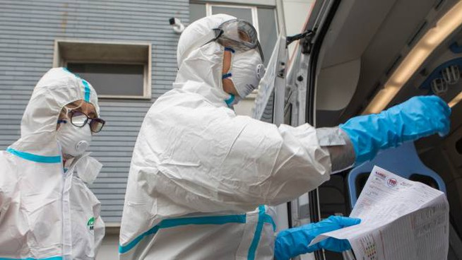 Medici e paramedici in ambulanza con protezioni coronavirus