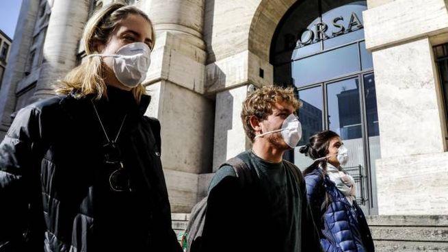 Persone con mascherine in piazza Affari (Ansa)