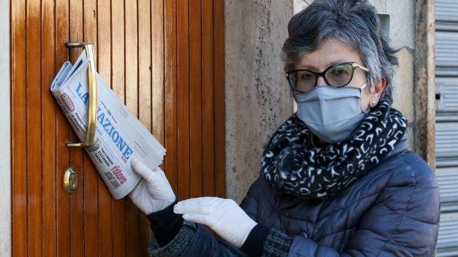 Un'edicolante con la mascherina consegna La Nazione a casa dei lettori