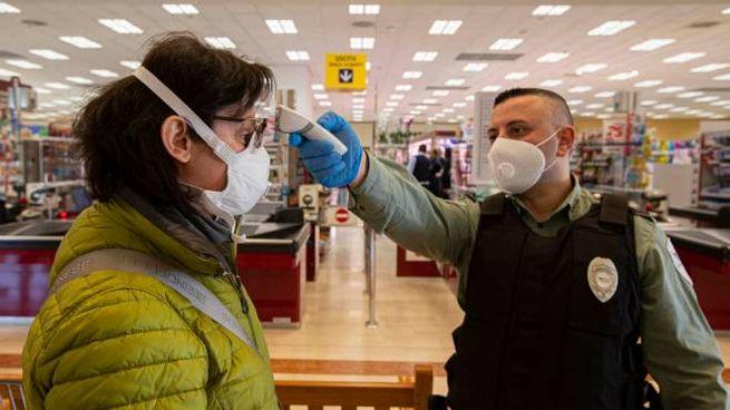 Misurazione della temperatura prima di entrare in un supermercato (Ansa)