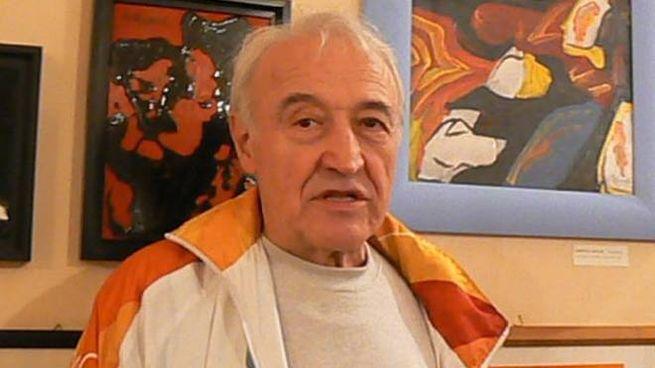 Oscar Ghidini davanti ad alcuni suoi quadri