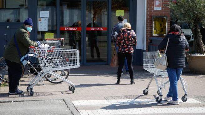 Gente in fila al supermercato per fare la spesa (Ansa)