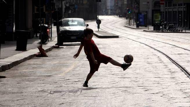 Un bambino gioca a palla in una strada deserta