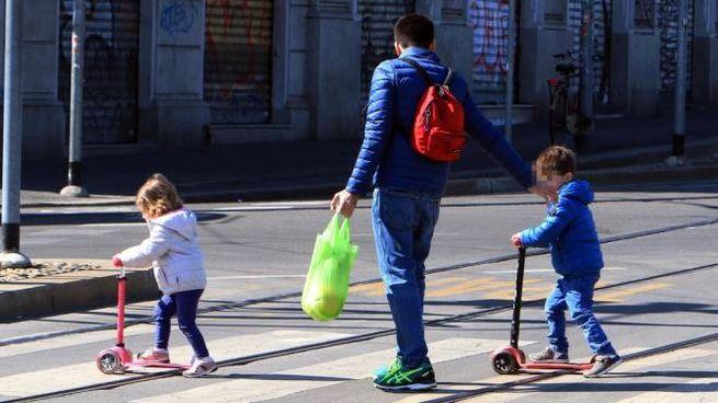 Bimbi portati dal papà a fare una passeggiata (Ansa)