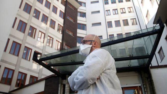 Un operatore sanitario davanti alle palazzine di una casa di riposo di Milano