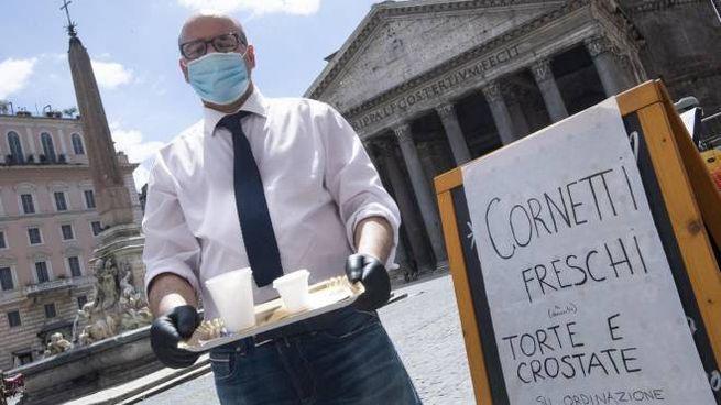 Un cameriere con tanto di guanti e mascherina a Roma (Ansa)
