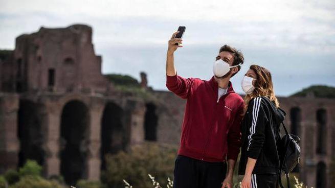Roma, una coppia posa per un selfie in mascherina (Ansa) davanti al Circo Massimo