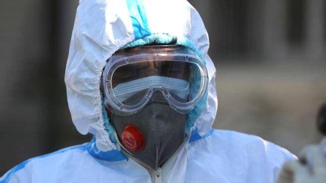 Un operatore sanitario indossa le protezioni anti Coronavirus (Ansa)