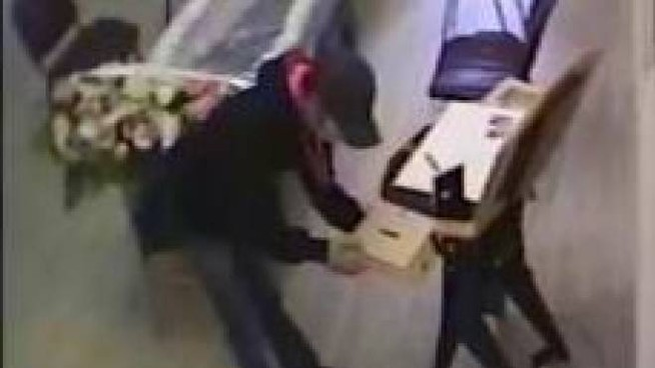 Il fotogramma che riprende l'uomo mentre porta via la cassettina delle offerte dalla camea mortuaria