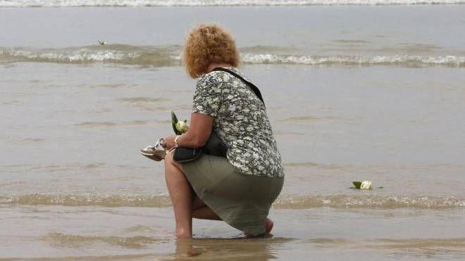 Una turista tedesca lancia fiori  per ricordare un'amica morta nello tsunami in Thailandia