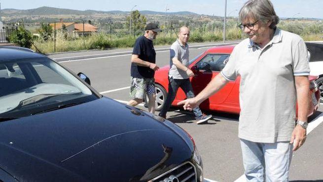 Uno dei residenti danneggiati mostra lo sfregio lasciato dai vandali sul cofano dell'auto