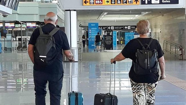 Due viaggiatori all'aeroporto 'Leonardo da Vinci' (Ansa)